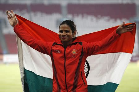 Athletics - 2018 Asian Games - Women's 100m Final - GBK Main Stadium – Jakarta, Indonesia – August 26, 2018 – Silver medallist Dutee Chand of India poses with her national flag during the medal ceremony. REUTERS/Darren Whiteside