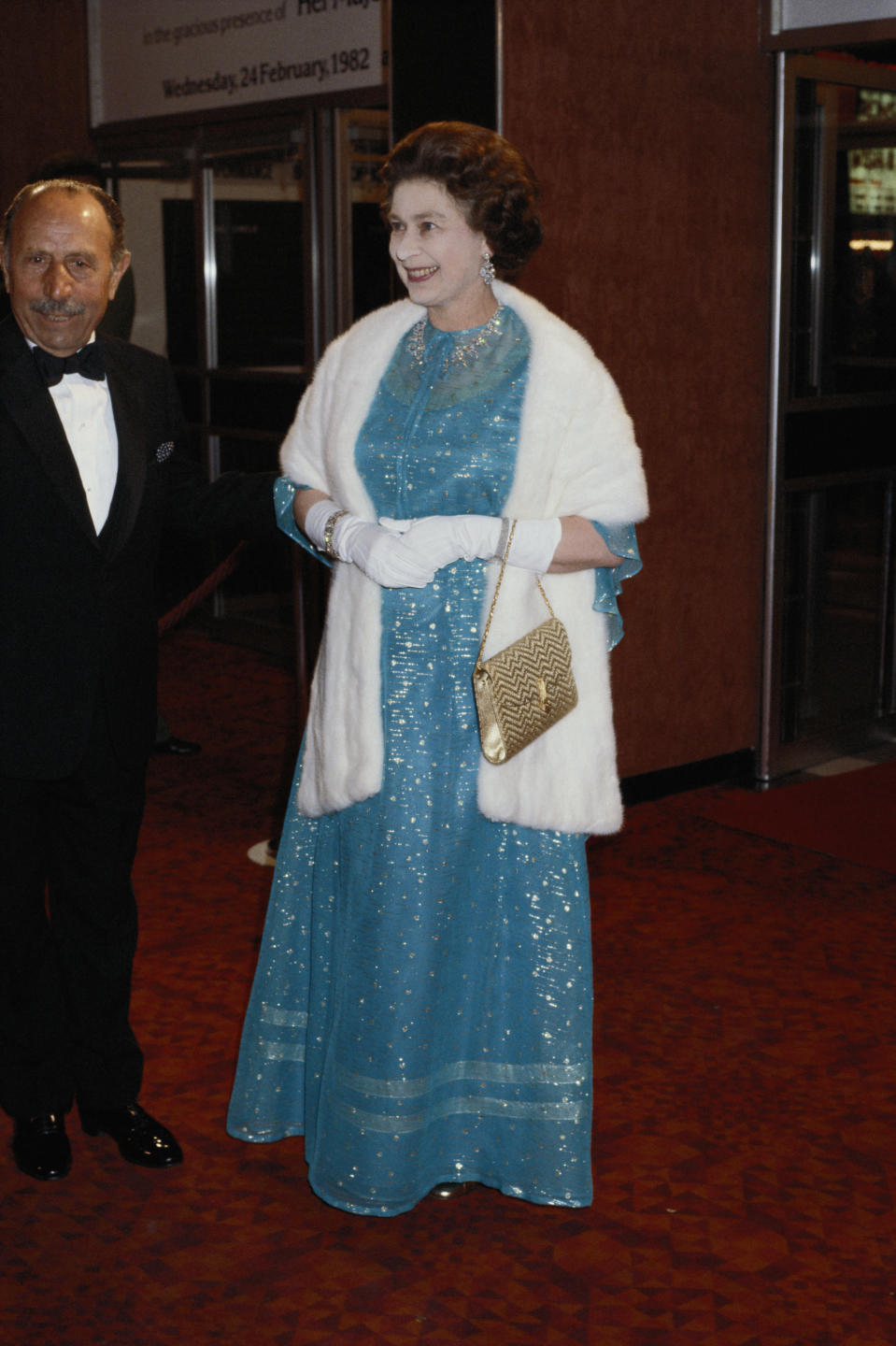 <p>Her Majesty wore a royal blue gown and white shawl for the red carpet back in 1982. <em>[Photo: Getty]</em> </p>