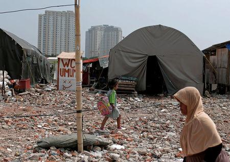 A student walks near a temporary shelter for people after her house was demolished last year, in Luar Batang area in Jakarta