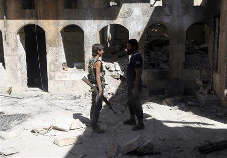 Ahmad Abu Layl (L), a 15 year-old fighter from the Free Syrian Army, chats with his father in Aleppo September 10, 2013. REUTERS/Hamid Khatib