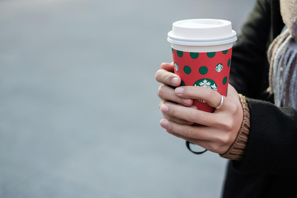 Woman hands holding hot Starbucks coffee paper cup, for Christmas and Happy New Year collection. Kunming, China, December 10, 2019