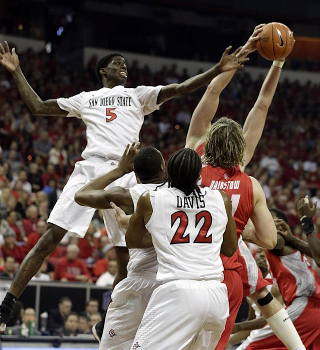 San Diego State's Dwayne Polee II, left, leaps for a rebound during the first half of an NCAA college basketball game against New Mexico for the Mountain West Conference tournament championship on Saturday, March 15, 2014, in Las Vegas. (AP Photo/Isaac Brekken)