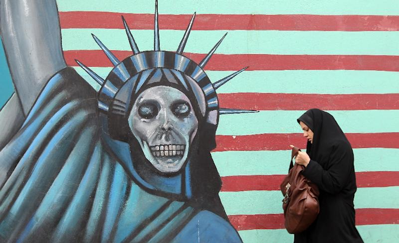 An Iranian woman walks past an anti-US mural painted on the wall of the former US embassy in Tehran (AFP Photo/Atta Kenare)