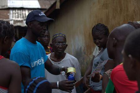 A UNICEF worker shares information on Ebola and best practices to help prevent its spread with residents of the Matam neighborhood of Conakry