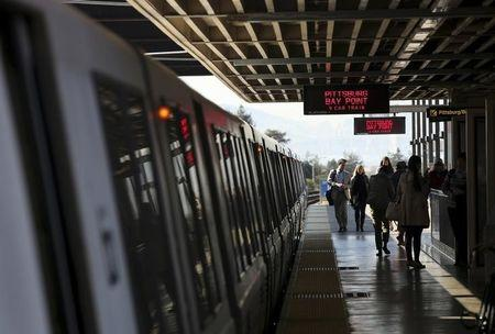 Passengers depart from a Bay Area Rapid Transit (BART) train at the Rockridge station in Oakland