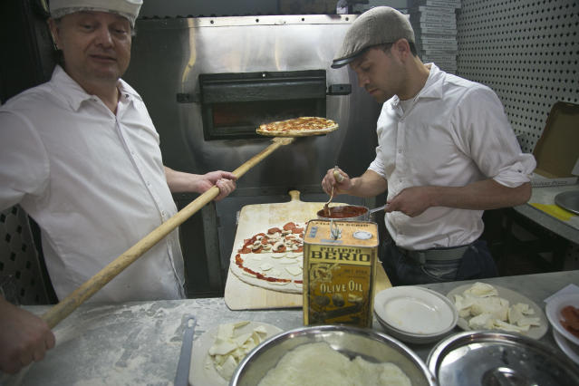 This June 12, 2013 photo shows Totonno's Pizzeria pizzaioli Michael Gammone, left, and John Raffaele baking in the same coal oven founded with the establishment 89 years ago in the Coney Island neighborhood in the Brooklyn borough of New York. The eatery has reopened after being closed 5 months from superstorm Sandy damage. (AP Photo/Bebeto Matthews)