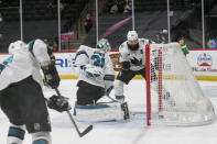 San Jose Sharks goalie Martin Jones, center, and defenseman Brent Burns, right, turn to watch the puck go into the goal after a shot by Minnesota Wild right wing Mats Zuccarello during the first period of an NHL hockey game Saturday, April 17, 2021, in St. Paul, Minn. (AP Photo/Craig Lassig)