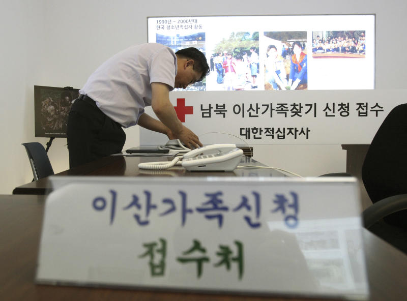 """A member of the Red Cross connects the inter-Korean communication line at the Korean Red Cross headquarters in Seoul, South Korea, Tuesday, June 11, 2013. The line was restored last week following North Korea's offer to hold talks with South Korea. The two Koreas will hold their highest-level talks in years Wednesday in an effort to restore scrapped joint economic projects and ease animosity marked by recent threats of nuclear war. The Korean writing reads """" Applications reception of separated families. """" (AP Photo/Ahn Young-joon)"""