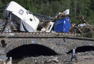 Caravans, cars and mobile homes that were swept away by the flood wave hang together on a bridge over the River Ahr, in Altenahr, western Germany, Sunday, July 18, 2021. Heavy rains caused mudslides and flooding in the western part of Germany. Multiple have died and are missing as severe flooding in Germany and Belgium turned streams and streets into raging, debris-filled torrents that swept away cars and toppled houses. (Boris Roessler/dpa via AP)