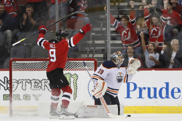 New Jersey Devils left wing Taylor Hall (9) celebrates a goal by Kyle Palmieri, in front of Edmonton Oilers goaltender Mikko Koskinen (19) during the first period of an NHL hockey game Thursday, Oct. 10, 2019, in Newark, N.J. (AP Photo/Kathy Willens)