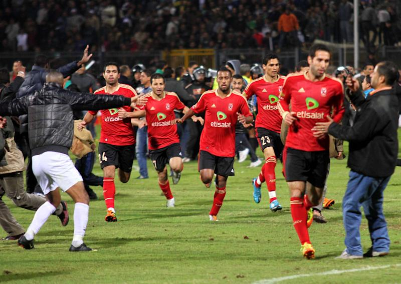 FILE - In this Wednesday, Feb. 1, 2012 file photo, players from the Egyptian Al-Ahly club run for safety during clashes following their soccer match against Al-Masry club at the soccer stadium in Port Said, Egypt. Egypt's top prosecutor has charged 75 people with murder and negligence in connection with a deadly soccer riot last month in the Mediterranean city of Port Said. (AP Photo/Ahmed Hassan, File)