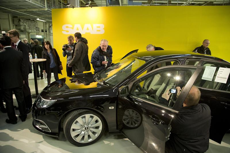 Reporters look at the first production Nevs (National Electric Vehicle Sweden) Saab 9-3 Aero at the Trollhattan factory in Sweden, Monday, Dec. 2, 2013. NEVS bought the remains of Swedish car maker SAAB and is focusing on electric vehicles. However the first car to leave the factory after it was restarted is a gasoline fueled 220 horsepower 2.0-liter turbo. (AP Photo/TT, Bjorn Larsson Rosvall) SWEDEN OUT