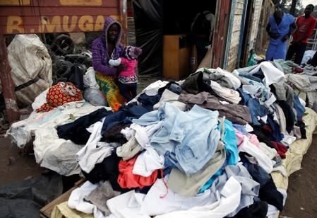 A woman sells old clothes near to a wall where it's written ''R. Mugabe'', at a market in Mbare township, Harare