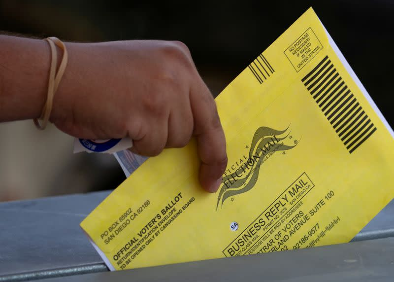 FILE PHOTO: An election worker places mail-in ballots into a voting box at a drive-through drop off location at the Registrar of Voters for San Diego County in San Diego, California
