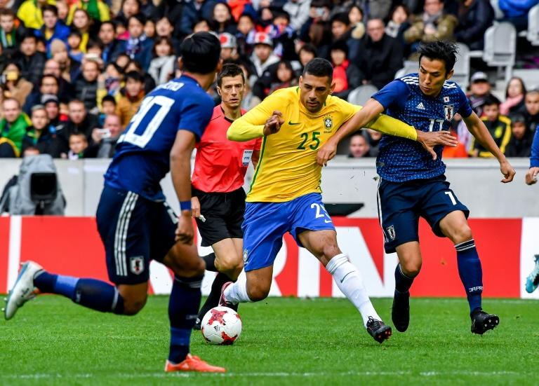 Brazil's Diego Souza (C) fights for the ball with Japan's Hasebe Makoto (R) during a their match in Villeneuve d'Ascq on November 10, 2017