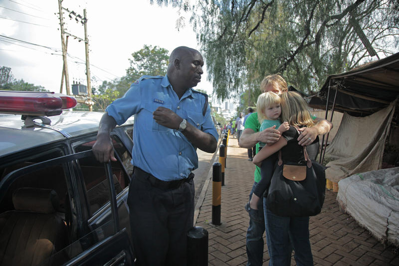 Lyndsay, centre right, embraces daughter Julia and husband Nick, partially seen, in a reunion that came after the couple had been separated for three hours inside a mall under attack by al-Shabab terrorists in Nairobi, Kenya on Saturday, Sept. 21, 2013. The couple, friends of an AP reporter, were texting and calling the AP reporter during the hostage crisis, blurring the lines between journalist and friend. (AP Photo/Georgina Goodwin)