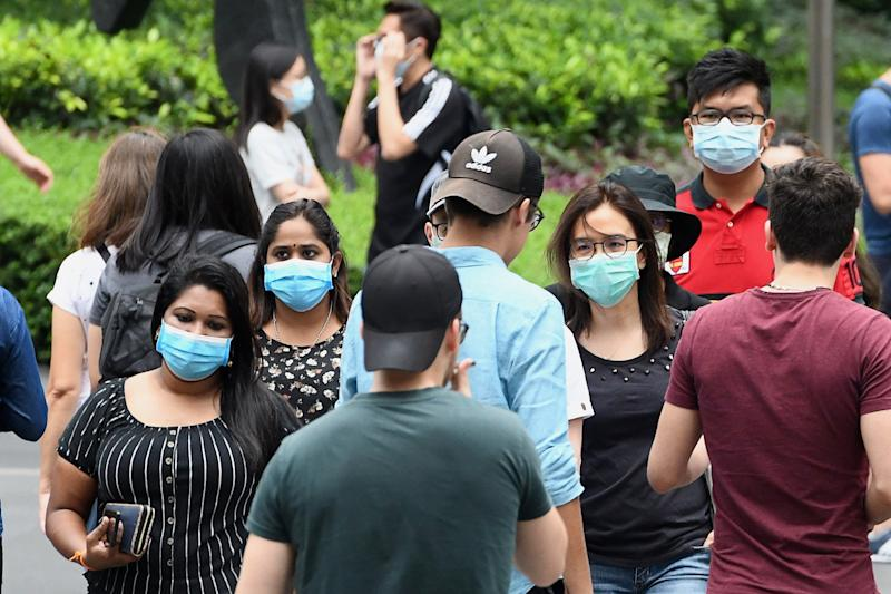This picture taken on April 5, 2020 shows people wearing face masks in the Orchard Road shopping district in Singapore. (Photo by Roslan RAHMAN / AFP) (Photo by ROSLAN RAHMAN/AFP via Getty Images)