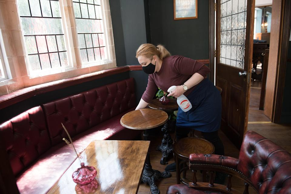 <p>Member of staff cleans table</p> (PA Wire)