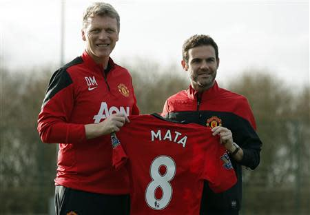 Manchester United's new signing Juan Mata (R) holds a club shirt with club manager David Moyes during a photocall at the club's Carrington training complex in Manchester, northern England, January 27, 2014. REUTERS/Phil Noble