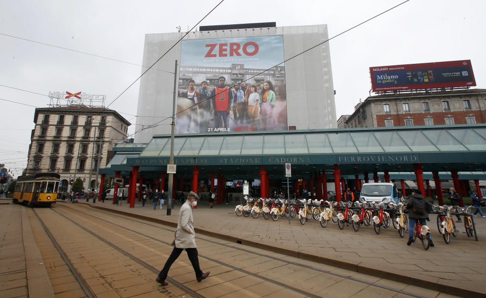 """A man walks under a poster advertising the TV Series """"Zero"""", at Cadorna square in Milan, Italy, Tuesday, April 27, 2021. The Netflix series """"Zero,"""" which premiered globally last month, is the first Italian TV production to feature a predominantly black cast, a bright spot in an otherwise bleak television landscape where the persistent use of racist language and imagery in Italy is sparking new protests. (AP Photo/Antonio Calanni)"""