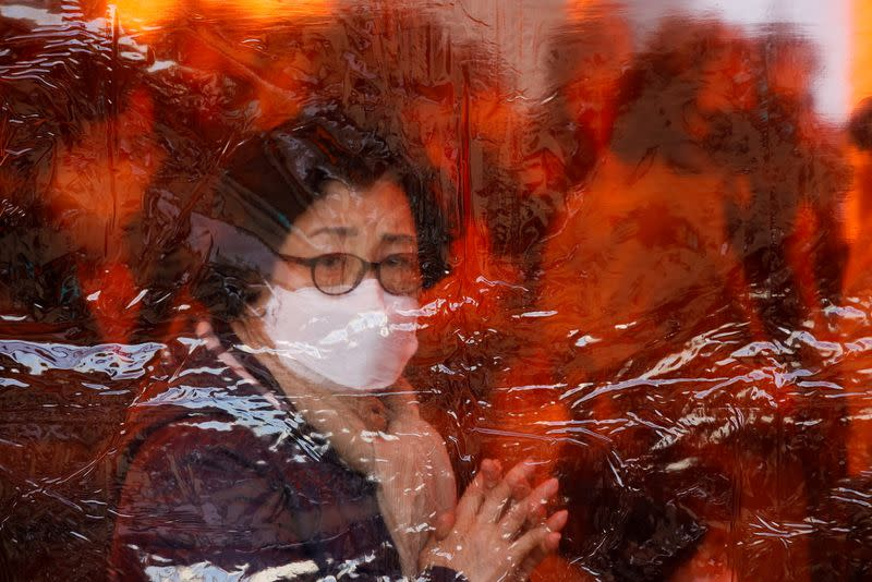 A mother prays for children's success in the college entrance examinations amid the coronavirus disease (COVID-19) pandemic, at a Buddhist temple in Seoul