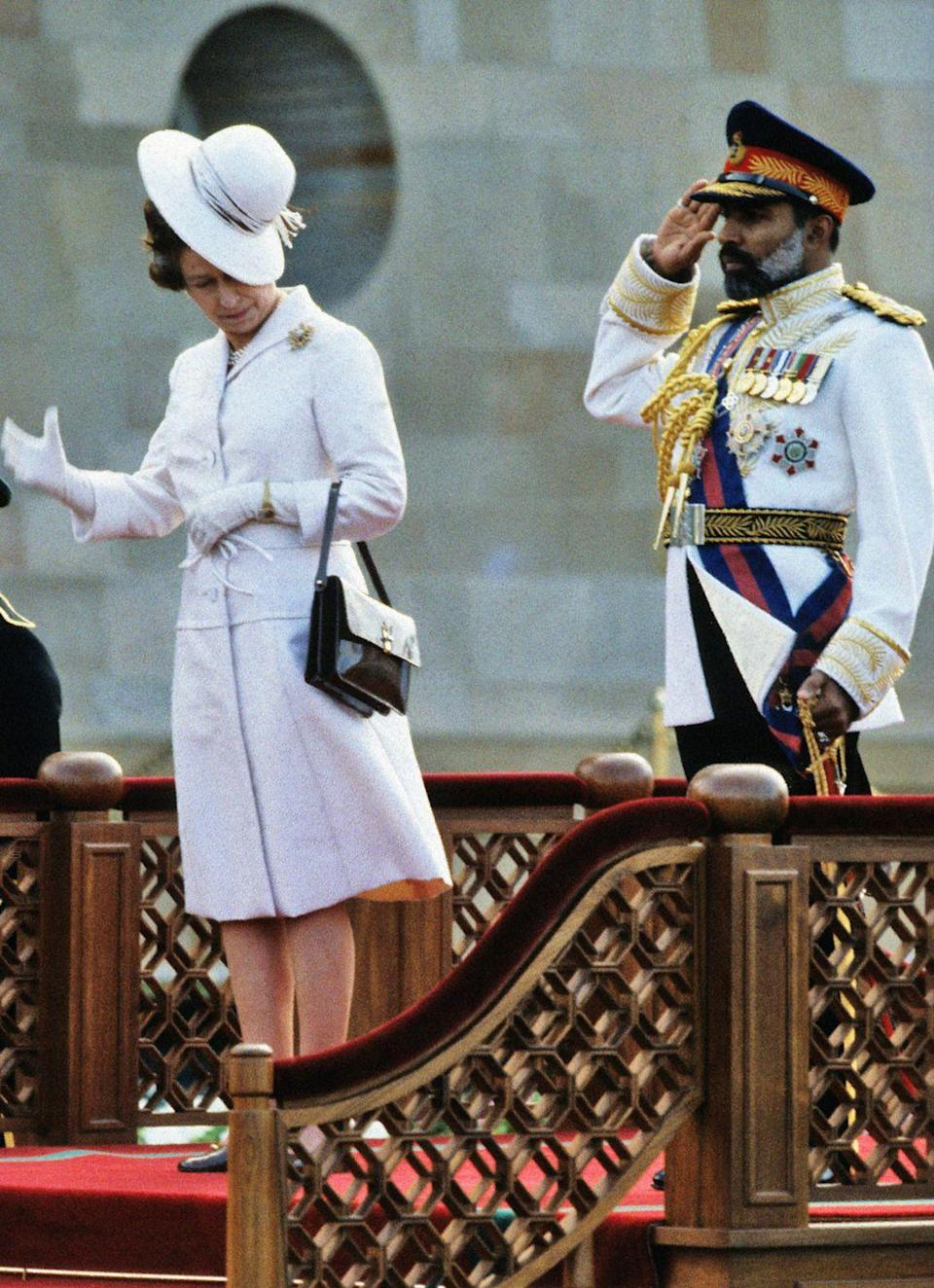 <p>Queen Elizabeth II fights a losing battle against the wind during a visit to Muscat, Oman. </p>