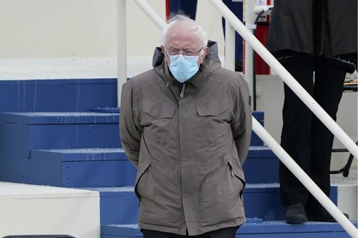 Sen. Bernie Sanders standing in a coat and face mask