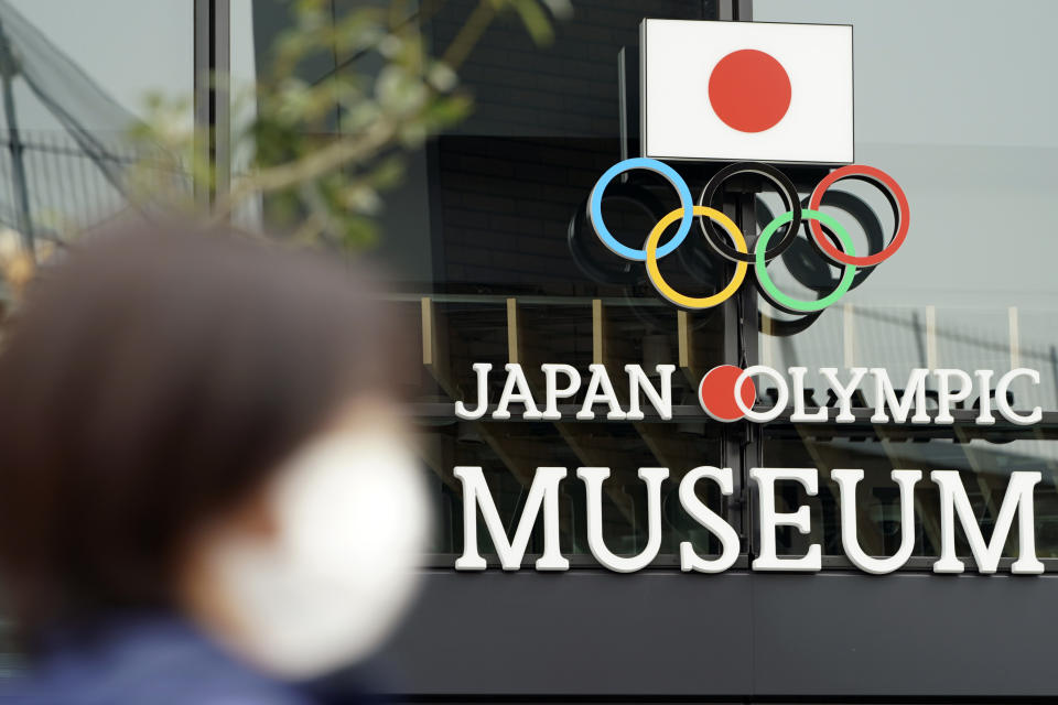 A woman wearing a mask against the spread of the new coronavirus walks in front of the Japan Olympic Museum building in Tokyo Tuesday, April 21, 2020. An open conflict broke out Tuesday between Tokyo Olympic organizers and the IOC over how much to divulge about who will pay for the unprecedented year-long postponement. (AP Photo/Eugene Hoshiko)