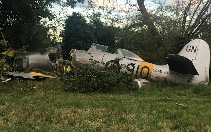 This dramatic photo shows the wreckage of a vintage British fighter plane The Hawker Sea Fury after it crashed during a routine flight in Button End near Duxford, Cambs - leaving the pilot and a passenger injured.See SWNS story SWCAcrash. This dramatic photo shows the wreckage of a vintage British fighter plane after it crashed during a routine flight - leaving the pilot and a passenger injured. The Hawker Sea Fury aircraft came down in a field at around 5.15pm yesterday evening (Tues), after having to make a forced landing, leading to the plane sustaining a fuel leak. The shocking photo shows the serious damage to the front of the plane, which appears to have been severed in two by the cockpit as it seemingly struck a tree on its way down. The pilot and a passenger both received medical attention at the scene, in Button End near Duxford, Cambs., after sustaining minor injuries in the crash. - Michael Hutchinson / SWNS.COM