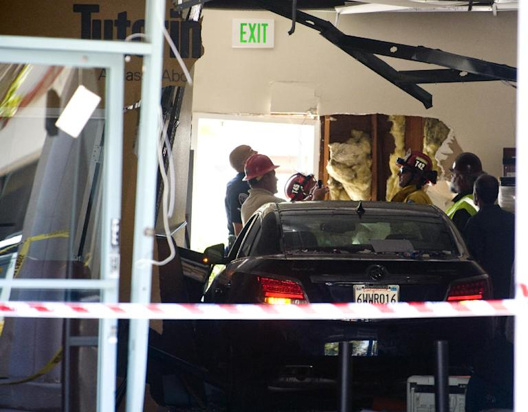 Authorities assess the damage at the scene where a car crashed into the Tutoring Club in Fountain Valley, Calif., on Monday, Aug. 19, 2013. Police say a 76-year-old man drove his car into the tutoring club, injuring five people, including two who were trapped underneath the vehicle. (AP Photo/The Orange County Register, Sam Gangwer)