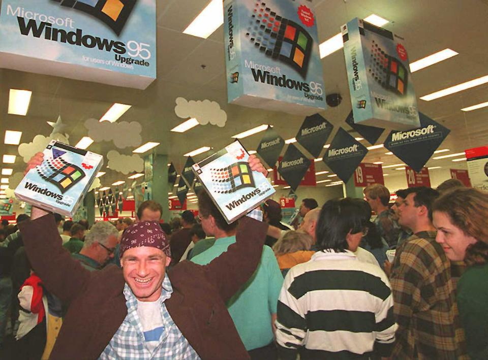 A giddy Australian customer holds aloft his two copies of Windows 95 in Syndey after the launch at midnight on August 24. (Getty)
