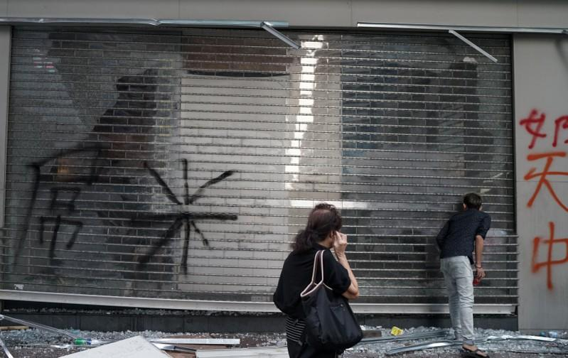 People inspect a shop which was vandalised during Sunday's anti-government protest in Hong Kong