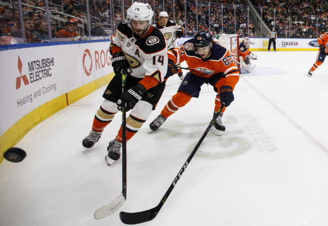 Anaheim Ducks' Adam Henrique (14) and Edmonton Oilers' Matthew Benning (83) reach for the puck during the third period of an NHL hockey game Saturday, Feb. 23, 2019, in Edmonton, Alberta. (Jason Franson/The Canadian Press via AP)