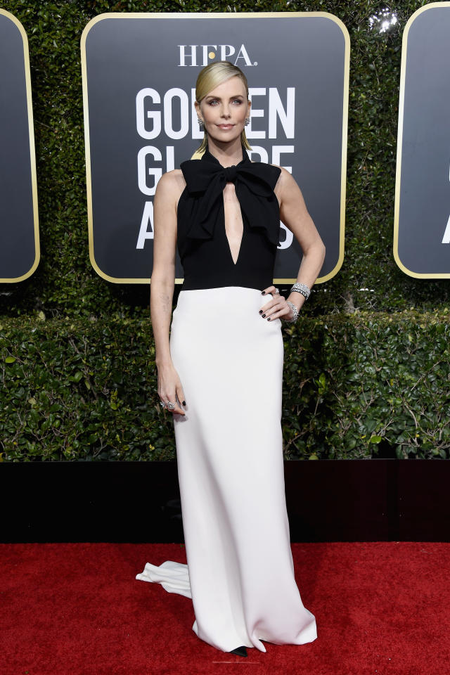 <p>Theron opted for a classic black and white Dior dress for the red carpet. Image via Getty Images. </p>