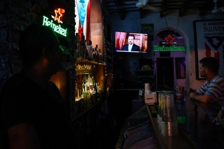 People watch a television broadcast of Puerto Rico's governor Ricardo Rossello's speech at a bar in San Juan