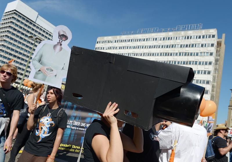 In this picture taken Sept. 7, 2013, a woman protests with a selfmade surveillance camera on her head during the demonstration 'in Berlin, Germany. German news weekly Der Spiegel reports Sunday Sept. 8, 2013 that the U.S. National Security Agency can access users' data on all major smartphones. The magazine cites internal documents from the NSA and its British counterpart GCHQ in which the agencies describe setting up dedicated teams to crack protective measures on iPhones, BlackBerry and Android devices. This data includes contacts, call lists, SMS traffic, notes and location data. (AP Photo/dpa,Rainer Jensen)