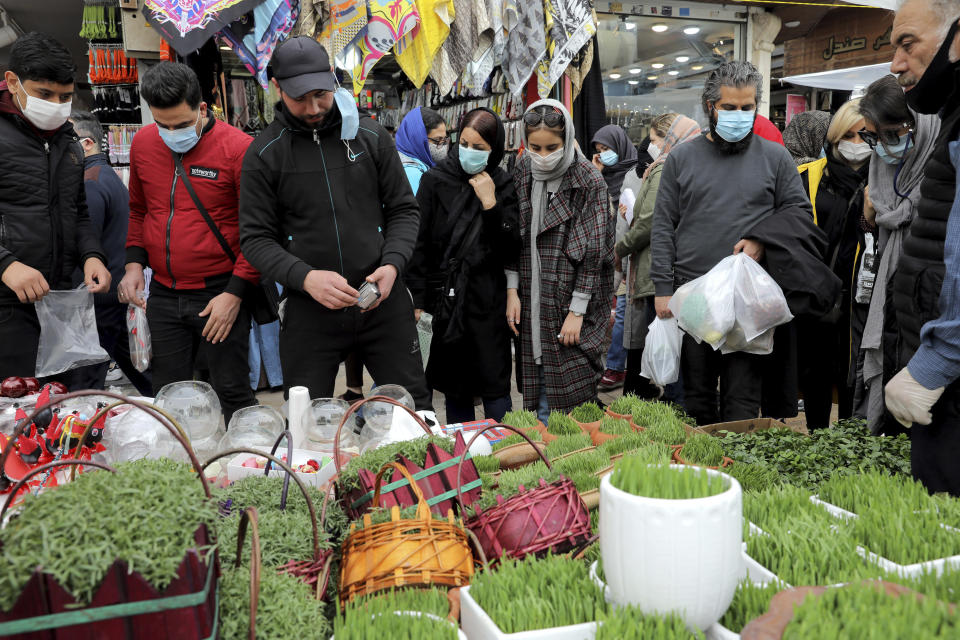"""Potential customers look at baskets of grass shoots, an item of the Persian New Year, or Nowruz, meaning """"New Day."""" in northern Tajrish Square, Tehran, Iran, Wednesday, March 17, 2021. (AP Photo/Ebrahim Noroozi)"""