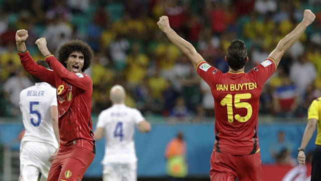 Belgium's Marouane Fellaini, left, and Daniel Van Buyten celebrate after the World Cup round of 16 soccer match between Belgium and the USA at the Arena Fonte Nova in Salvador, Brazil, Tuesday, July 1, 2014. Belgium won the match 2-1 after extra-time. (AP Photo/Julio Cortez)