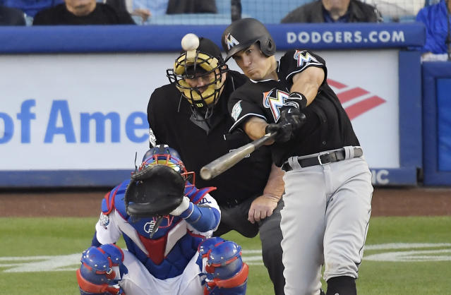 Miami Marlins' J.T. Realmuto, right, hits a solo home run as Los Angeles Dodgers catcher Yasmani Grandal, left, and home plate umpire Joe West watch during the sixth inning of a baseball game Wednesday, April 25, 2018, in Los Angeles. (AP Photo/Mark J. Terrill)