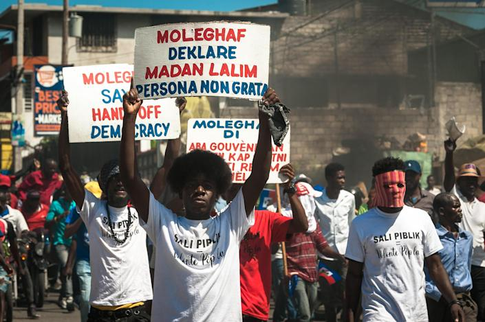 Haitians carry banners during a protest to denounce the draft constitutional referendum carried by the President Jovenel Moise on March 28, 2021 in Port-au-Prince, Haiti. / Credit: Sabin Johnson/Anadolu Agency via Getty Images