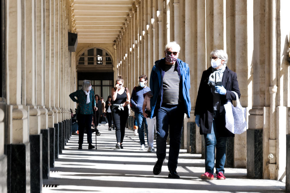 Paris : People walking under arch, near Comédie française, Palais Royal, colonnes de Buren, during epidemic Covid19 in Europe. This life scene is few days after the Covid 19 lockdown during spring 2020.  Paris in France, May 16th, 2020.