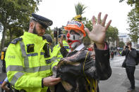 A climate activist is detained by police as others gather at Parliament Street in London, Monday, Oct. 7, 2019. London Police say they've arrested 21 climate change activists over the past few days as the Extinction Rebellion group attempts to draw attention to global warming. (AP Photo/Alberto Pezzali)