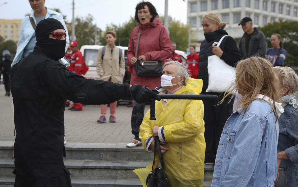 Women argue with a police officer during an opposition rally to protest the official presidential election results in Minsk, Belarus, Sunday, Sept. 27, 2020. Tens of thousands of demonstrators marched in the Belarusian capital calling for the authoritarian president's ouster, some wearing cardboard crowns to ridicule him, on Sunday as the protests that have rocked the country marked their 50th consecutive day. (AP Photo/TUT.by)