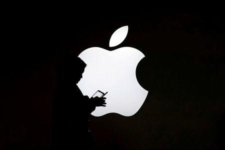 FILE PHOTO: A woman looks at the screen of her mobile phone in front of an Apple logo outside its store in Shanghai