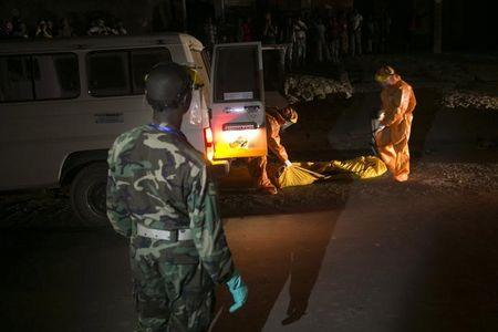 Health workers collect the body of a suspected Ebola victim from a street in the town of Koidu