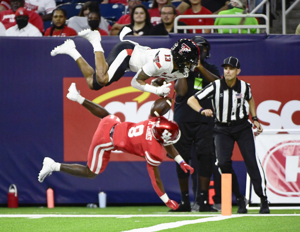 Texas Tech wide receiver Erik Ezukanma (13) is knocked out of bounds by Houston cornerback Marcus Jones (8) during the first half of an NCAA college football game Saturday, Sept. 4, 2021, in Houston. (AP Photo/Justin Rex)