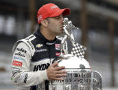FILE - Tony Kanaan, of Brazil, kisses the Borg-Warner Trophy as he poses during the traditional photo session for the winner of the Indianapolis 500 auto race at the Indianapolis Motor Speedway in Indianapolis, in this Monday, May 27, 2013, file photo. Superstar Racing Experience was conceptualized as a series for former greats who still had the skills and desire to compete and square off in identically prepared cars at six of America's classic short tracks. Ray Evernham and Tony Stewart took great care in extending invites to the made-for-TV league they had co-created. They thoughtfully pulled in a a dozen of the most iconic names in modern day motorsports. (AP Photo/Michael Conroy, File)