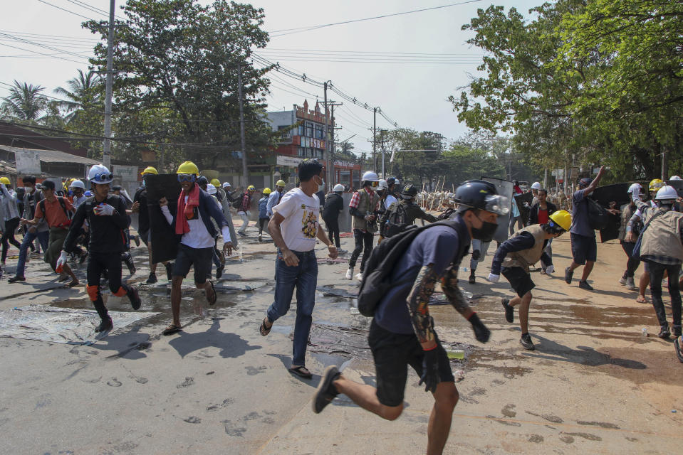 Anti-coup protesters scatte after police fire sound grenades and fire rubber bullets in Yangon, Myanmar, Thursday, March 11, 2021. Amnesty International accused Myanmar's military government on Thursday of increasingly using battlefield weapons against peaceful protesters and conducting systematic, deliberate killings. (AP Photo)
