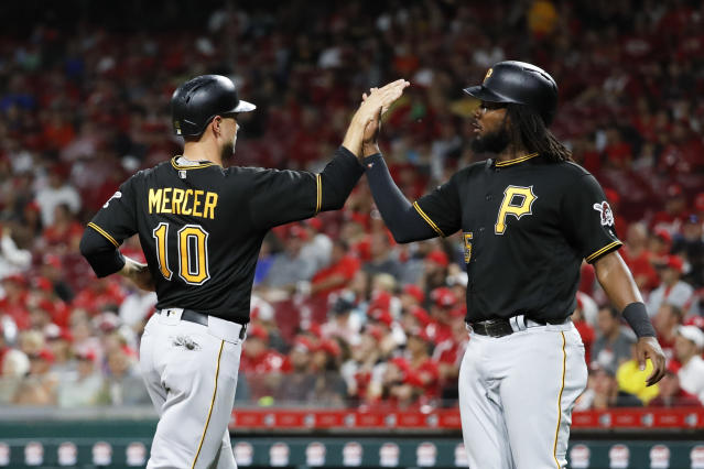 Pittsburgh Pirates' Jordy Mercer (10) celebrates with Josh Bell, right, after scoring on a two-run single by Nick Kingham off Cincinnati Reds relief pitcher Michael Lorenzen in the sixth inning of a baseball game, Saturday, July 21, 2018, in Cincinnati. (AP Photo/John Minchillo)