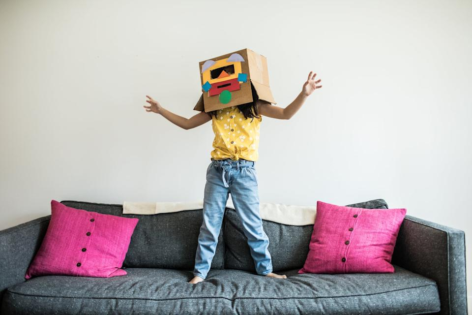 Young girl wearing robot costume at home